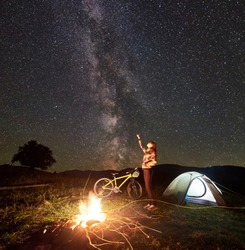 Young woman tourist resting at night camping, pointing at incredible beautiful evening sky full of stars and Milky way, standing near burning campfire, illuminated tent, mountain bike. Tourism concept