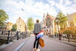 Young woman tourist standing back with dutch flag on the bridge enjoying beautiful morning view on the old town of Amsterdam city