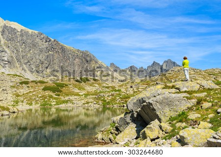 Young woman tourist standing on top of a rock on shore of alpine lake in summer landscape of Starolesna valley, High Tatra Mountains, Slovakia