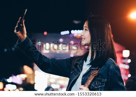 Young woman tourist taking selfie photo in night street. Female traveler and photographer takes picture for her blog.