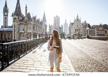 Shutterstock Young woman tourist walking the bridge in the old town of Gent city durnig the sunrise in Belgium