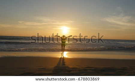 Young woman tourist with backpack walking on beach to the ocean at sunset and raised hands. Girl hiker going on sandy shore to the sea and enjoying freedom during summer vacation. Rear back view. #678803869