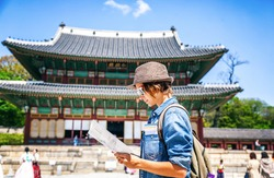 Young woman tourist with map in hand on the background of Asian architecture, travel to Korea, Seoul Asia
