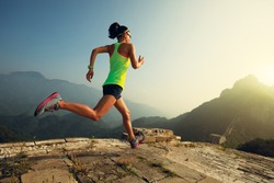 Young woman trail runner running at great wall on the top of mountain