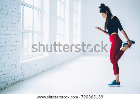 Young woman training in gym watch video from web page online on mobile for stretching muscles of lower body,sportswoman warming up and blogging in networks on smartphone standing near publicity area
