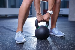 Young woman training in gym with heavy weights.Strong young female athlete exercising with dumbbell in  sport club.Strength and healthy lifestyle.Fit girl exercise indoor