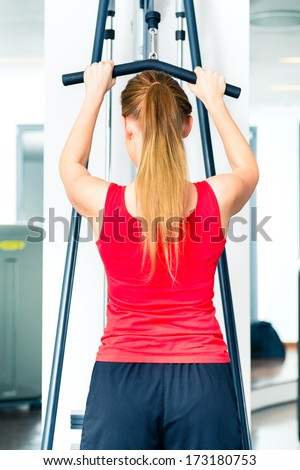 Young woman training on machine in gym or sport center