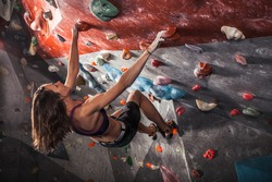 Young woman training on practice climbing wall indoor