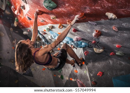 Young woman training on practice climbing wall indoor #557049994