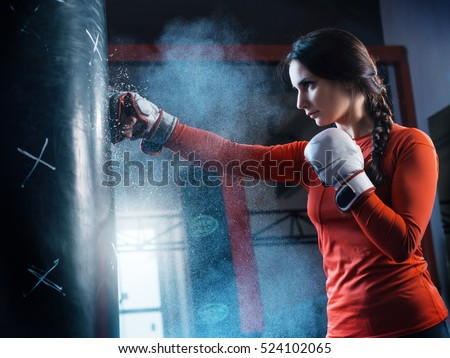Young woman training punch boxing gloves for punching bag. Girl making Strong kick. CrossFit.