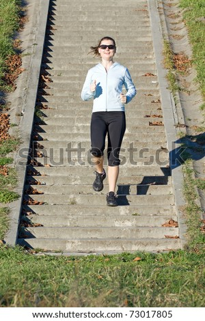 Young woman trains running on concrete stairs outdoors.