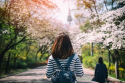 Young woman traveler backpacker traveling into N Seoul Tower at Namsan Mountain in Seoul City, South Korea.