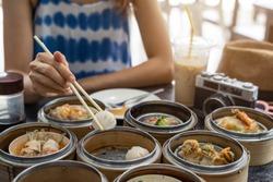 Young woman traveler eating local food(dim sum) at phuket, Thailand