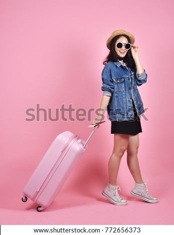 Young woman traveler holding pink suitcase and passport document over pink background, Journey and travel concept. #772656373