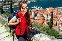 Young woman traveler in red vest with backpack on the Lovcen mountain in old city Kotor, Montenegro