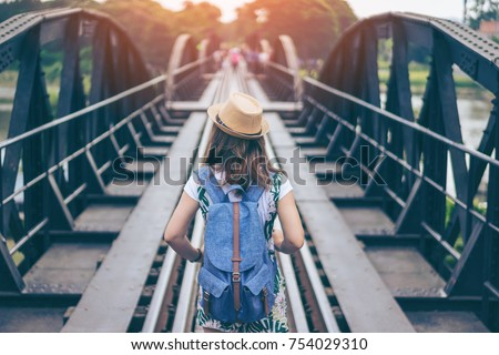 Young woman traveler is traveling at Bridge on River Kwai in Kanchanaburi, Thailand. The bridge is built during World War 2 by prisoners of war of Japanese.