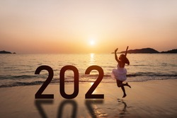 Young woman traveler jumping at the beach celebrating New Year 2021 at sunset