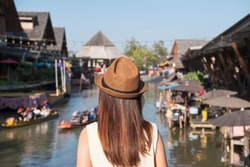 Young woman traveler looking at floating market in Thailand, Travel lifestyle concept