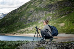 Young woman traveler professional photographer takes a picture of the landscape on the camera on a tripod, Norway, beautiful northern nature