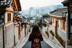 Young woman traveler traveling into Bukchon Hanok Village at Seoul city, South Korea. Bukchon Hanok Village is home to hundreds of traditional houses.