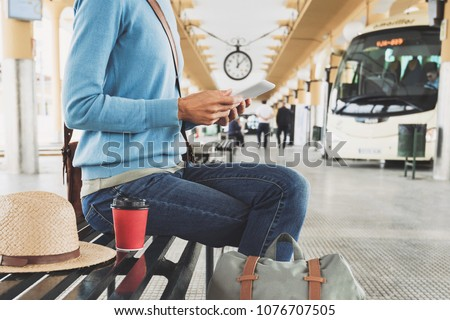 Young woman traveler waiting for a bus on a bus station and using digital tablet, travel and active lifestyle concept