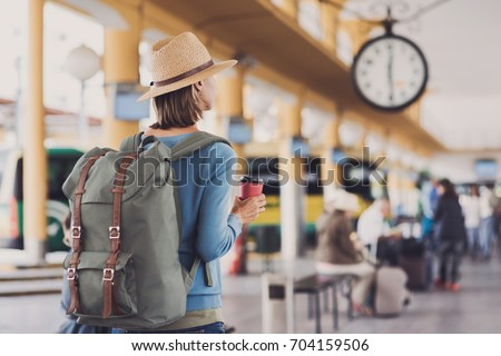 Shutterstock Young woman traveler waiting for a bus on a bus station, travel and active lifestyle concept