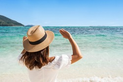 Young woman traveler wearing sunglasses covering face by hand to protect UV rays from the sun at tropical sandy beach on sunny day, Skin care and eyes protect concept