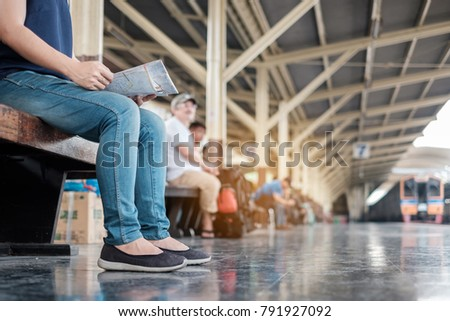 Young woman traveler with backpack looking to map while waiting for train, Asian backpacker sitting on railway platform at Bangkok train station. Holiday, journey, trip and summer Travel concept - Shutterstock ID 791927092