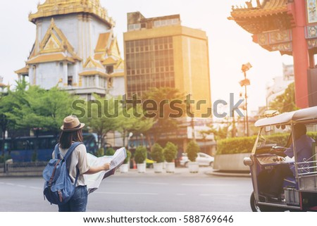 Young woman traveler with sky blue backpack and hat looking the map with tuk tuk Thailand background from china town Bangkok. Traveling in Bangkok Thailand. Travel concept #588769646