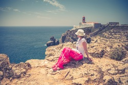 Young woman traveler with white hat and red dress sitting at Cabo de Sao Vicente Cape Saint Vincent cliff stone rocks and looking at Atlantic ocean horizon in sunny summer day, lighthouse background