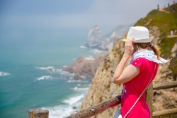 Young woman traveler with white hat and red dress staying near wooden fence at Cabo da Roca Cape Roca cliff and looking at Atlantic ocean endless horizon in sunny summer day, stone rocks background