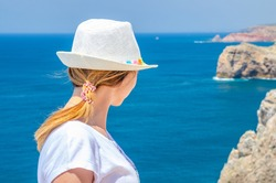 Young woman traveler with white hat and shirt staying at Cabo de Sao Vicente Cape Saint Vincent cliff and looking at Atlantic ocean endless horizon in sunny summer day, stone rocks background