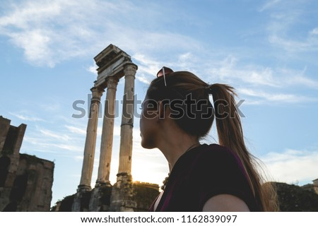 Young woman traveling around the most important landmarks in Rome, Italy. Roman Forum.