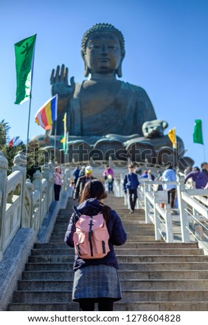Young woman traveling backpacker, Asian traveler visit the Tian Tan or Big Buddha located at Po Lin Monastery in Ngong Ping Lantau Island. landmark and popular for tourist attractions in Hong Kong