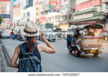 Young Woman traveling backpacker with hat, Asian traveler standing on Yaowarat road or Chinatown of Bangkok, landmark and popular for tourist attractions in Thailand. Travel concept