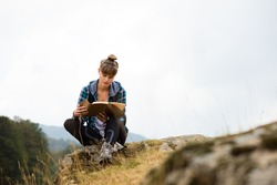 young woman traveling with her backpack in the mountains, sitting on a rock and reading a book or a journal