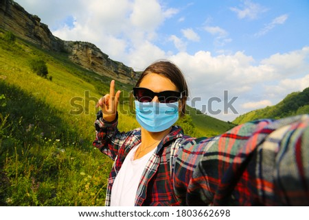 Young woman traveller wearing face mask outside at the nature and taking selfie at the mountains in Caucasus Russia.