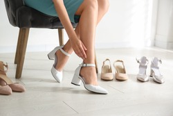 Young woman trying on shoes indoors, closeup