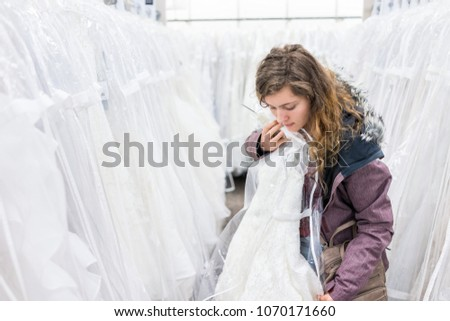 Young woman trying on wedding dress in boutique discount store, many white garments hanging on rack hangers row #1070171660