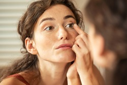 Young woman trying to apply contact lenses in front of a mirror. Young woman trying on new contact lenses. Close up of a girl trying on beauty medical contact-lenses.