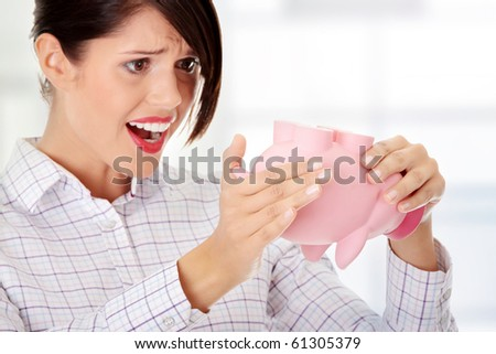 Young woman trying to get money from her piggy bank