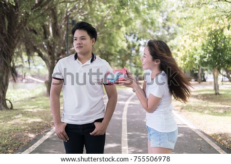 Young woman trying to reconcile his boyfriend offering gift , woman holding gift for try reconcile him
