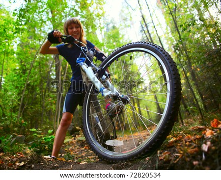 Young woman trying to ride on a bicycle in forest's offroad