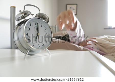 Young woman turning off alarm clock, motion blur on hand to exaggerate action, white copy space beneath