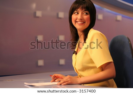 Young woman TV reporter smiling and looking back while preparing for the news presenting