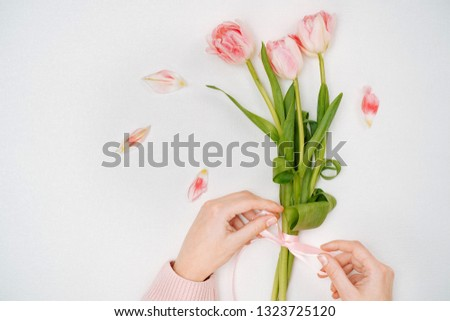 Young woman tying a ribbon on a bouquet of pink tulips.