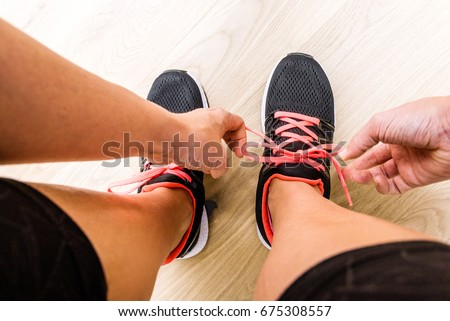 Young woman tying laces of running shoes before training Stock foto ©