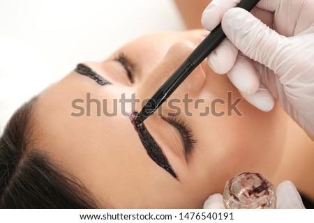 Young woman undergoing eyebrow correction procedure in beauty salon, closeup