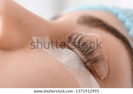 Young woman undergoing procedure of eyelashes lamination in beauty salon, closeup
