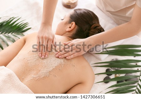 Young woman undergoing treatment with body scrub in spa salon Foto stock ©